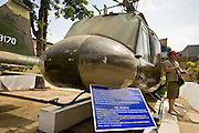 09 MARCH 2006 - HO CHI MINH CITY, VIETNAM: A tourist stands next to an old American helicopter at the War Remnants Museum in Ho Chi Minh City (Saigon), the former capital of South Vietnam. The War Remnants Museum displays American weapons and material captured by North Vietnamese and Viet Cong forces during the US war in Vietnam. PHOTO BY JACK KURTZ