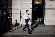 Passer-by and a City cafe in sunlight on King William Street in the City of London, the capital's financial district and oldest quarter.