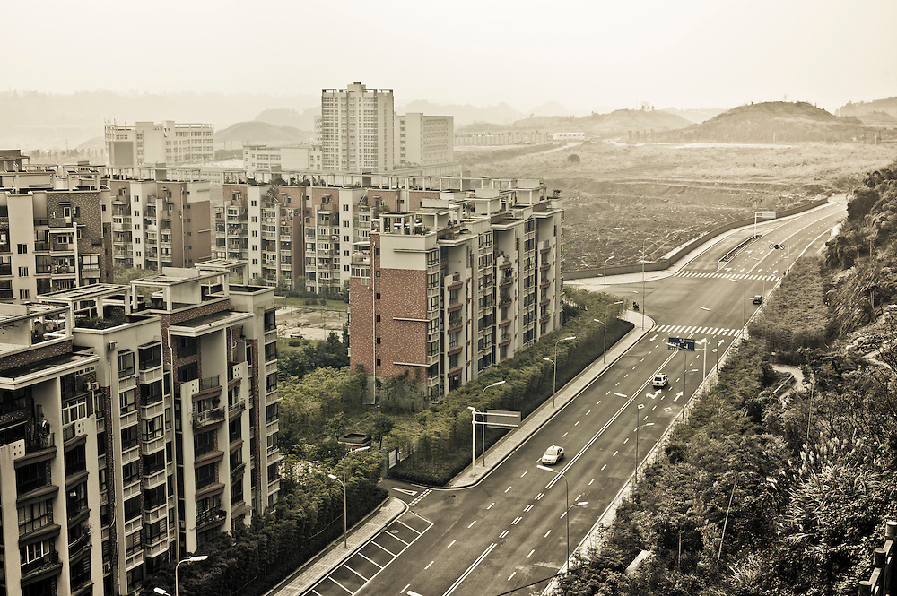 CHONGQING, CHINA - JAN 20, 2011: New buildings and road at the foot of the Jinyun mountain in Bei Bei district, Chongqing. These superblocks exemplify China's urbanisation and are usually built after the city government lays out a system of arterial roads.