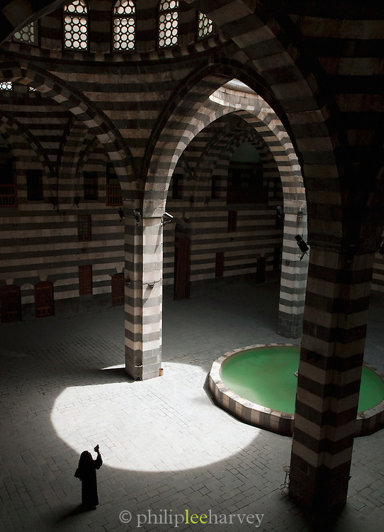 A woman takes photographs in Khan As'ad Pasha, a caravanserai in the Old City of Damascus, Syria