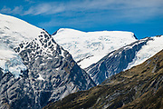 The Dart Glacier is seen at center, beyond glacier-clad Mt Edward on left in Dart Valley. Photographed on the descent from Rees Saddle via Snowy Creek, in Mount Aspiring National Park, Otago region, South Island of New Zealand.