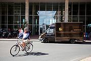 In Rotterdam fietst een man op een elektrische fiets met een helm door de Kop van Zuid. Een voertuig van UPS staat voor De Rotterdam.<br /> <br /> In Rotterdam a man on an electric bike cycles at the Kop van Zuid.