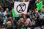 Extinction Rebellion climate change activists sit down blocking the road whist singing songs as sites around Westminster are blocked on 8th October 2019 in London, England, United Kingdom. Extinction Rebellion is a climate group started in 2018 and has gained a huge following of people committed to peaceful protests. These protests are highlighting that the government is not doing enough to avoid catastrophic climate change and to demand the government take radical action to save the planet.