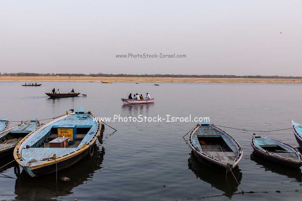Brightly colored row boats lined up on the Ganges river in Varanasi, India