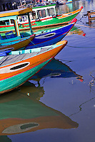 Colourful boats and their reflections on Hoi An's Thu Bon river.