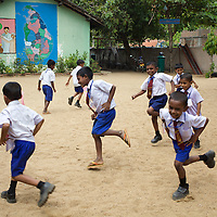 """Pupils play games at the K.M. Vivekanana Vidalayam school in Kalmunai, Ampara Dist. <br /> <br /> The Kalmunai community was tsunami affected and for six months the school grounds became an IDP camp. The school continued teaching during this time in a local temple. The school is known as a """"Child Friendly School"""". Unicef has provided sanitary facilities: boys and girls toilets and hand washing area. Immediately after the tsunami, Unicef supplied books to the school. Unicef has trained teachers in child friendly education and in the establishment of a Children's Brigade. Children's Brigades are a means of promoting hygiene practice in pupils and encouraging them to disseminate messages of hygiene practice and awareness in the wider community.<br /> <br /> Photo: Tom Pietrasik<br /> Ampara District, Sri Lanka<br /> September 29th 2009"""