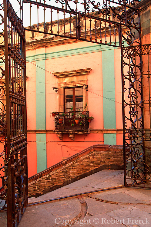 MEXICO, COLONIAL CITIES, GUANAJUATO architectural details in the city center with wrought iron gate and colorful house and window beyond