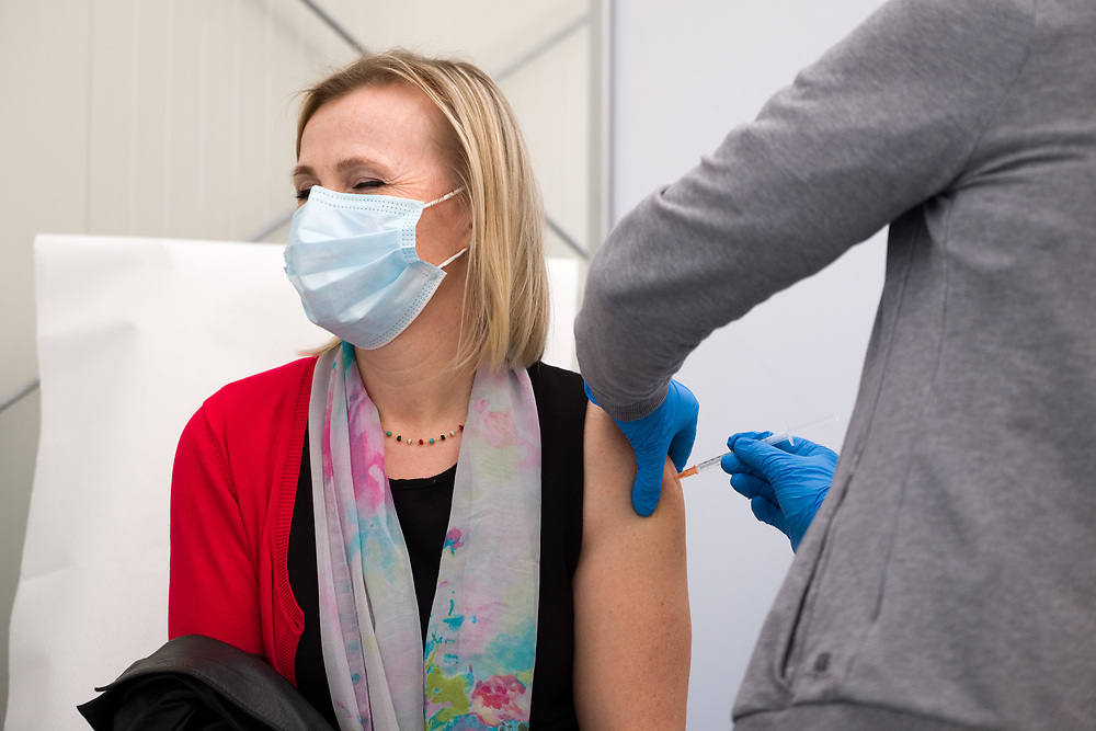 """A woman receives a dose of the AstraZeneca COVID-19 vaccine in the Covid Vaccine Center on March 4, 2021 set up in the """"Ferrari-Orsi"""" barracks of the Brigata Bersaglieri Garibaldi (Bersaglieri Garibaldi Brigade) in Caserta, southern Italy, as part of vaccinations for teachers and school staff. The center is the largest in the Campania region, with 26 stations where up to three thousand vaccines can be administered per day."""