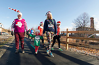 Betty Collins, Isabella Cartier and Johannah McApine walk in the Santa Shuffle with The Downtown Gym on Sunday morning.  (Karen Bobotas/for the Laconia Daily Sun)
