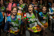 """Two young girls carry the baton as they run on the 20th Korrika. Kadreita. (Basque Country). March 31, 2017. The """"Korrika"""" is a relay course, with a wooden baton that passes from hand to hand without interruption, organised every two years in a bid to promote the basque language. The Korrika runs over 11 days and 10 nights, crossing many Basque villages and cities. This year was the 20th edition and run more than 2500 Kilometres. Some people consider it an honour to carry the baton with the symbol of the Basques, """"buying"""" kilometres to support Basque language teaching. (Gari Garaialde / Bostok Photo)"""