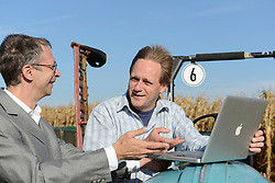 Farmer and businessman talking and checking information in laptop on cornfield, Bavaria, Germany