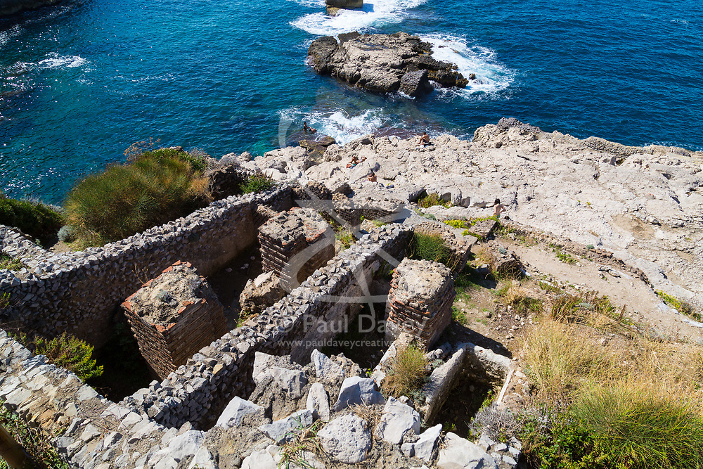 Sorrento, Italy, September 18 2017. The ancient Roman ruins of Villa di pollio Felice near Sorrento, Italy dwarf sunbathers on the rocks below. © Paul Davey