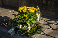 Yellow Chrysanthemums and a candle on a grave at Rakowicki cemetery in Krakow, Poland 2019.