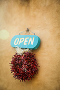SHOT 12/29/15 4:53:32 PM - A chile ristra with an open sign welcoming guests into a shop in Taos, N.M. Taos, N.M. is a town in northern New Mexico's high desert, bounded by the Sangre de Cristo Mountains and incorporated in 1934 with a population of around 6,000. It's known for historic adobe buildings like Taos Pueblo, a multistory adobe complex inhabited by Native Americans for centuries. A longtime artist colony, Taos also offers many galleries and museums showcasing regional artwork. (Photo by Marc Piscotty / © 2015)