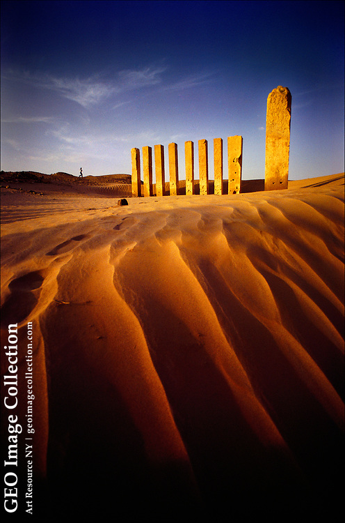 In the desert outback of Yemen near Marib, relics of a lost civilization jut from the sand.  These golden pillars and a few slabs of inscribed rock are all that remains of a moon-god temple built by the ancient Sabaeans--a kingdom that prospered for more than a thousand years and is thought to have once been ruled by the Queen of Sheba.