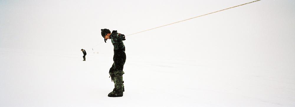 Fisherman dragging nets under the ice, Lake Baikal, Siberia, Russia