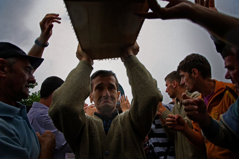 Crowds of men gather to help carry remains of Srebrenica victims to their gravesites at the Potocari memorial.