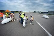 De VeloX2 (links) en de Velox worden klaar gemaakt, terwijl Ellen van Vugt in de VeloXx voorbij komt. Het Human Power Team Delft en Amsterdam (HPT) traint op de RDW baan in Lelystad met de VeloX2 voor de recordpoging in september. Het HPT hoopt dan in Amerika meer dan 133 km/h te rijden over 200 meter.<br /> <br /> The VeloX2 (left) and the VeloX are being prepared for starting, while Ellen van Vugt is passing with the VeloXx, Human Powered Team Delft and Amsterdam (HPT) is training at the RDW test track in Lelystad with the VeloX2 for the record attempt in september.