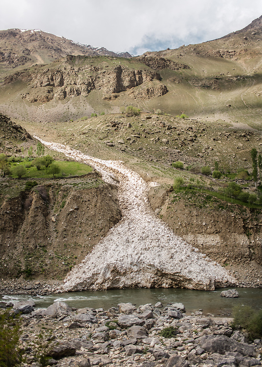 An avalanche above the Shakhdara river. <br /> <br /> The town of Khorog (2200m), is the capital of the Gorno-Badakhshan Autonomous Province (GBAO) in Tajikistan. It is situated in the Pamir Mountains (ancient Mount Imeon) at the confluence of the Gunt and Panj rivers.<br /> The city is bounded to the south and to the north by the deltas of the Shakhdara and Gunt rivers, respectively. The two rivers merge in the eastern part of the city flow through the city, dividing it almost evenly until its delta in the river Panj, also being known as Amu Darya, or in antiquity the Oxus on the border with Afghanistan. Khorog is known for its beautiful poplar trees that dominate the flora of the city.<br /> Khorog is one of the poorest areas of Tajikistan, with the charitable organization Aga Khan Foundation providing almost the only source of cash income. Most of its inhabitants are Ismaili Muslims.<br /> <br /> Tajikistan, a mountainous landlocked country in Central Asia. Afghanistan borders it to the south, Uzbekistan to the west, Kyrgyzstan to the north, and People's Republic of China to the east. Tajikistan also lies adjacent to Pakistan separated by the narrow Wakhan Corridor.<br /> Tajikistan became a republic of the Soviet Union in the 20th century, known as the Tajik Soviet Socialist Republic.<br /> It was the first of the Central Asian republic to gain independence in December 1991.