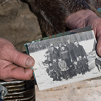 North of the Arctic Circle in Russia, Rema Chuprova, a nomadic Komi reindeer herder,  displays a photo of her family from the 1950's.  Today, there are no remaining young married couples and no children in this group.  Few modern women want to live on the tundra, and this threatens imminent collapse of their lifestyle.