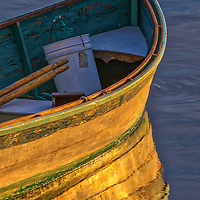 New England harbor fine art of a dinghy painted in warm hues at sunrise in Gloucester on Cape Ann, Massachusetts.<br /> <br /> Beautiful Cape Ann sunrise photography pictures of a dinghy at Gloucester Harbor are available as museum quality photography prints, canvas prints, acrylic prints, wood prints or metal prints. Fine art prints may be framed and matted to the individual liking and interior design decorating needs.<br /> <br /> Good light and happy photo making!<br /> <br /> My best,<br /> <br /> Juergen