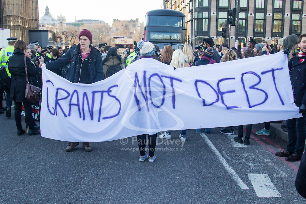 """Westminster, London, January 19th 2016. Students hold an """"emergency protest"""" in Parliament Square and later blocking Westminster Bridge, against the cutting of maintenance grants. """"It took just 18 MPs 90 minutes to scrap maintenance grants for the million poorest students, without a debate in Parliament in a backroom committee"""" PICTURED:. Protesters block Westminster Bridge. ///FOR LICENCING CONTACT: paul@pauldaveycreative.co.uk TEL:+44 (0) 7966 016 296 or +44 (0) 20 8969 6875. ©2015 Paul R Davey. All rights reserved."""