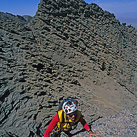 Mountaineer Sam Lightner, Jr. climbs treacherous conglomerate rock on Shipton's Arch in the arid Kara Tagh Mountains next to the Taklimakan Desert near Kashagar (Kashi) in Xinjiang Province, China.