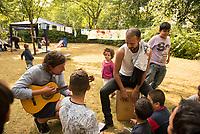 DEU, Deutschland, Germany, Berlin, 19.08.2015: Der Musiker Jan Weigel (links mit Gitarre), Freiwilliger Helfer der Initiative Moabit Hilft, macht zusammen mit einem Flüchtling und Flüchtlingskindern Musik auf dem Gelände des Landesamts für Gesundheit und Soziales (LaGeSo), hier befindet sich die Zentrale Aufnahmeeinrichtung des Landes Berlin für Asylbewerber.