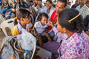 09 JULY 2014 - ARANYAPRATHET, SA KAEO, THAILAND: A family of Cambodian migrant workers eat their lunch before going into the Thai Immigration One Stop Service Center in Aranyaprathet on the Thai-Cambodian border after they registered for temporary ID documents. More than 200,000 Cambodian migrant workers, most undocumented, fled Thailand in early June fearing a crackdown by Thai authorities after a coup unseated the elected government. Employers have been unable to fill the vacancies created by the Cambodian exodus and the Thai government has allowed them to return. The Cambodian workers have to have a job and their employers have to vouch for them. The Thai government is issuing temporary ID cards to allow them to travel openly to their jobs. About 800 Cambodian workers came back to Thailand through the Aranyaprathet border crossing Wednesday. The Thai government has opening similar service centers at three other crossing points on the Thai-Cambodian border.    PHOTO BY JACK KURTZ