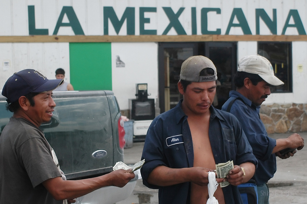 Migrant farm workers count their day's earnings in  Immokalee, FL,  Apr.16, 2003.