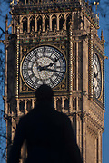 The silhouetted statue of Sir Robert Peel and the clockface containing the Big Ben bell in the Elizabeth Tower of the British parliament, on 17th January 2017, in London England. The Elizabeth Tower previously called the Clock Tower named in tribute to Queen Elizabeth II in her Diamond Jubilee year – was raised as a part of Charles Barrys design for a new palace, after the old Palace of Westminster was largely destroyed by fire on the night of 16 October 1834. The new Parliament was built in a Neo-gothic style, completed in 1858 and is one of the most prominent symbols of both London and England. Sir Robert Peel, was a British statesman and member of the Conservative Party, served twice as Prime Minister of the United Kingdom and twice as Home Secretary. He created the modern police force and officers known as bobbies and peelers.