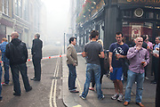 Friday afternoon drinkers enjoy a glass in the smoke filled streets. A fire broke out on Dean Streen in Soho, Central London on Friday afternoon. The fire, in a five storey building in the heart of the city raged with firefighters struggling to get the blaze under control. In the nearby streets workers finishing early stood in the smoke filled streets having an end-of-the-week beer in the ghostly atmosphere.