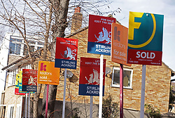 """File photo dated 01/03/15 of a row of Sold, For Sale and Let signs displayed outside houses, as housing market activity has reached a plateau as consumers face a period of """"belt tightening"""", according to a trade body."""
