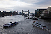 View of barges, Thames Clipper ferry and boats on the River Thames looking towards Tower Bridge on 16th January 2020 in London, England, United Kingdom.
