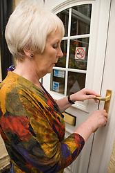 Older woman locking her front door,