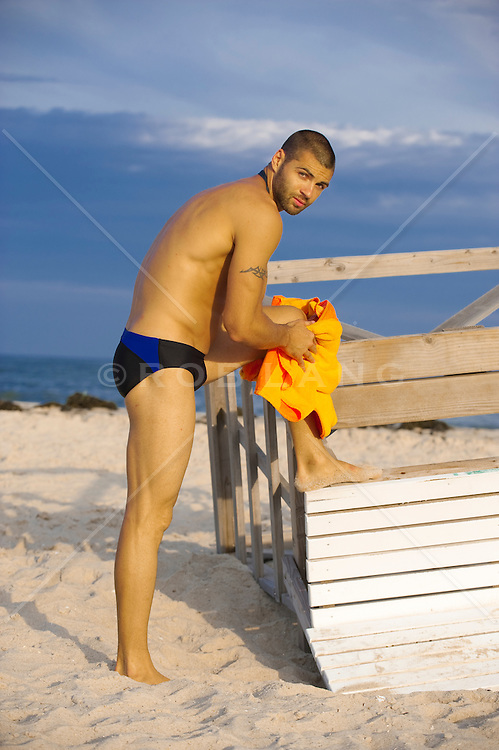Man in a speedo toweling off at the beach