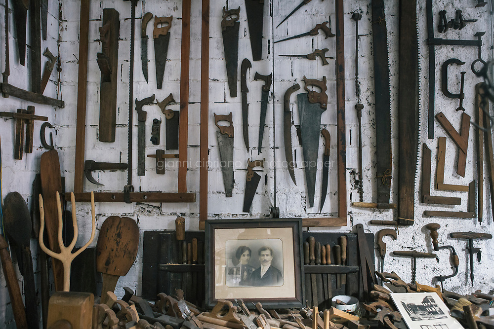 MANAROLA, ITALY - 31 MAY 2017: A collcetion of tradiional Ligurian daily life items is seen here in Anselmo Crovara's  Memory Archive, housed in his own attic in Manarola, Italy, on May 31st 2017. Mr Crovara learned to build dry stone walls when he was a little boy.<br /> <br /> Given its jagged coastline and manifold mountainous chains, Italy is believed to hold a record in Europe with an estimated 300,000 hectares of terracing, and 170,000 kilometers of dry stone walls— 20 times the length of the Great Wall of China.<br /> Liguria, the narrow half-moon shaped region along the northern<br /> Thyrrenian sea, has the highest concentration, and terracing is in<br /> poor shape there. In Vernazza, almost half of the terracing is in<br /> ruins.<br /> <br /> Terraced vineyards, apple and lemon groves horizontally run around the green slopes of the Cinque Terre. The stone walls have allowed such vital cultivation in the area and prevented land slides. Since the 1960s, the ancient walls have been largely<br /> abandoned, posing hydro-geological threats to the same villages during<br /> heavy rains and, in general, as time passes.<br /> <br /> Since the 2012 flood - when tons of mud invaded the<br /> village's main road, shops and and homes, isolating the area and<br /> taking three lives - Margherita Ermirio has agreed with the various land lords to take<br /> over 6,000 square meters of land parcels that needed to be cleaned up,<br /> in order to fix them and thus prevent land slides, but also to show to<br /> the younger generations that agriculture is still possible in the<br /> Cinque Terre.