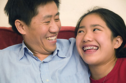 Father and daughter sitting together at home; smiling,