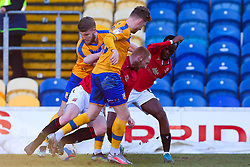Jason Law and George Maris of Mansfield Town challenge Liam Gibson and Carlos Mendes Gomes of Morecambe for possession - Mandatory by-line: Ryan Crockett/JMP - 27/02/2021 - FOOTBALL - One Call Stadium - Mansfield, England - Mansfield Town v Morecambe - Sky Bet League Two