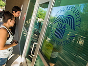 01 OCTOBER 2013 - PHOENIX, AZ: People read the note on the door of the Social Security Administration in Phoenix on the first day of the government shutdown. The US government closed most non-essential federal services Tuesday. The shutdown is be the first in the US in 17 years. More than 700,000 federal government workers could be sent home on unpaid leave, with no guarantee of back pay once the deadlock is over.    PHOTO BY JACK KURTZ