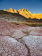 Sunset illuminates the Badlands Wall above cracked mud near Ben Reifel Visitor Center in Badlands National Park, South Dakota, USA. The intricately carved cliff of the Badlands Wall constantly retreats as it erodes and washes into the White River Valley below.