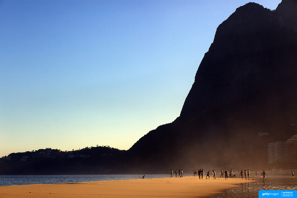 Locals play on the beach in the late afternoon light at Sao Conrado beach, Rio de Janeiro,  Brazil. 8th July 2010. Photo Tim Clayton..The beaches of Rio de Janeiro, provide the ultimate playground for locals and tourists alike. Beach activity is in abundance as beach volley ball, football and a hybrid of the two, foot volley, are played day and night along the length and breadth of Rio's beaches. .Volleyball nets and football posts stretch along the cities coastline and are a hive of activity particularly at it's most famous beaches Copacabana and Ipanema. .The warm waters of the Atlantic Ocean provide the ideal conditions for a variety of water sports. Walkways along the edge of the beaches along with exercise stations and cycleways encourage sporting activity, even an outdoor gym is available at the Parque Do Arpoador overlooking the ocean. .On Sunday's the main roads along the beaches of Copacabana, Leblon and Ipanema are closed to traffic bringing out thousands of people of all ages to walk, run, jog, ride, skateboard and cycle more than 10 km of beachside roadway. .This sports mad city is about to become a worldwide sporting focus as they play host to the world's biggest sporting events with Brazil hosting the next Fifa World Cup in 2014 and Rio de Janeiro hosting the Olympic Games in 2016...