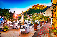 """""""Breakfast at dawn on the veranda of Albergo California Positano""""...<br /> <br /> There was only one occasion that I was really able to pre-plan taking photos at sunrise and that was during the last day of three in Positano. It takes much planning, logistics, and familiarity to figure the best locations and the proper angles and positions of the sun. My third morning was ideal and fortuitous as it began raining about 10:00 am which gave me perfect clouds for sunrise, finally ending with a very cold wind just in time for sunset. This image is one of the rare photos of a slumbering Positano in the dewing morning around 6:00 am at the end of May….the beginning of peak tourist season. By 8:00 am, this tiny seaside village is bustling with tourists and shop owners, and restaurateurs trying to satisfy every need. All in all, Positano was by far the plushest of all the locations I visited in Italy, and I was blessed to witness everything in full bloom."""