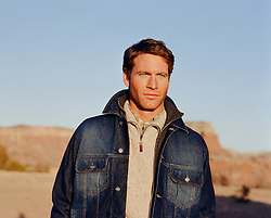 portrait of a handsome man in a jeans jacket outdoors in the New Mexico desert