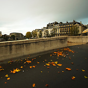 Man crossing one of the bridges of the Seine river with Notre Dame on the background