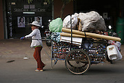 Recycling worker, Phnom Penh. Woman pulling trolley packed with cardboard, aluminium drink cans, plastic bottles she has collected on the streets and bought on the sidewalk. Like many rural peasants who have left the countryside in search of earning a decent living, she ended up as recycling worker on Phnom Penh's city streets. They earn a few dollars a day from selling by weight the plastic bottles, aluminium cans and cardboard they collect during a days work. Usually they work from the mid afternoon until midnight, sorting through the rubbish on the streets. They take what they collect to small sorting houses on the edge of the city.