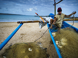 August 3, 2017 - Kuta, Bali, Indonesia - A man stows his nets on his outrigger canoe on Jimbrana Beach in Kuta. The beach is close to the airport and a short drive from other beaches in southeast Bali. Jimbrana was originally a fishing village with a busy local market. About 25 years ago, developers started building restaurants and hotels along the beach and land prices are rising. The new emphasis on tourism is changing the nature of the area but the fishermen are still busy very early in the morning. (Credit Image: © Jack Kurtz via ZUMA Wire)