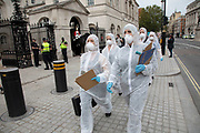 Extinction Rebellion 'crime scene investigators' in white suits and masks walk along Whitehall to investigate areas of ecocide in a performance on 7th September 2020 in London, United Kingdom. The 20 investigators were protesting at the Brazilian government's alleged involvement in ecocide in the Amazon, and the UK government's ecocide along the HS2 route. Extinction Rebellion is a climate change group started in 2018 and has gained a huge following of people committed to peaceful protests. These protests are highlighting that the government is not doing enough to avoid catastrophic climate change and to demand the government take radical action to save the planet.