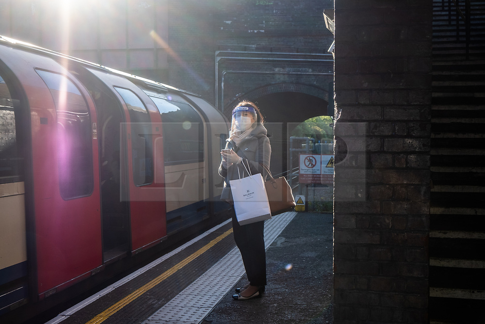 © Licensed to London News Pictures. 14/05/2020. London, UK. A commuter at Hanger Lane tube station wears a face mask visor waits for a train during morning rush hour. The government relaxed some rules allowing people to travel to work if they are unable to work from home. Photo credit: London News Pictures