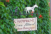 A wrought iron painted sign that illustrates the theme of champagne and wine production: A man and a white horse ploughing a vineyard, Champagne Jean Bliard, Culture Biologique (organic production), the village of Hautvillers in Vallee de la Marne, Champagne, Marne, Ardennes, France
